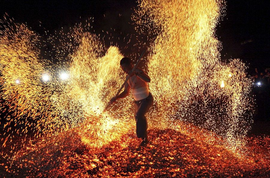 600053-a-man-sweeps-burning-charcoal-as-he-participates-in-the-traditional-ritual-called-lianhuo-or-fire-wa